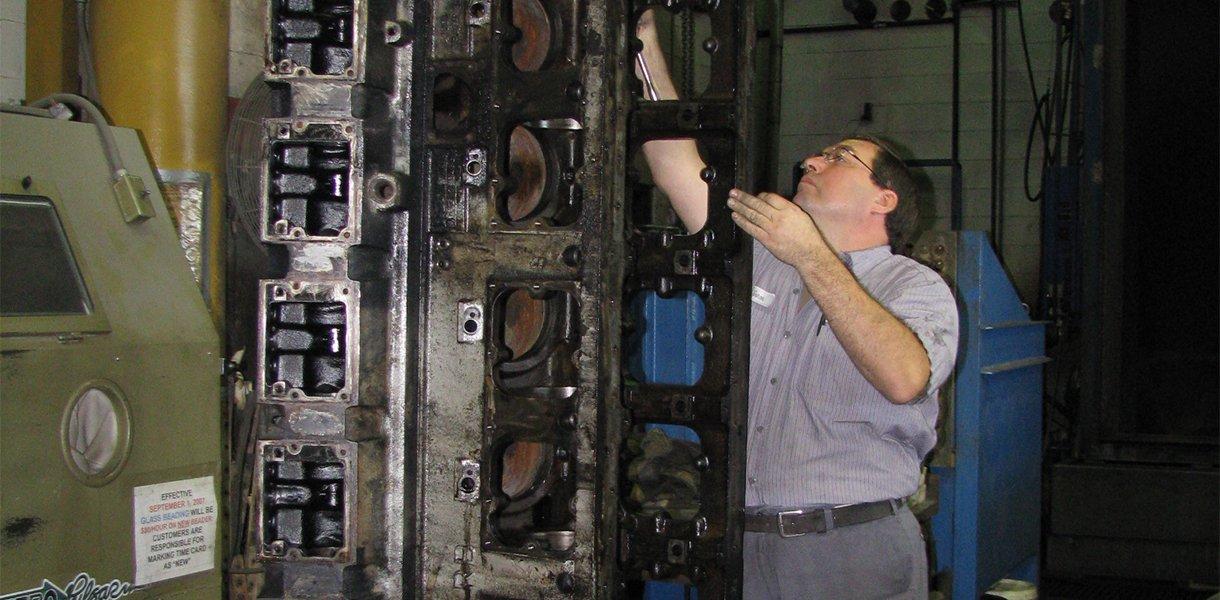 A Rutt's Machine, Inc. technician cleaning a disassembled engine
